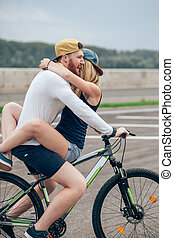 Happy man giving girlfriend a lift on his crossbar of bike ...