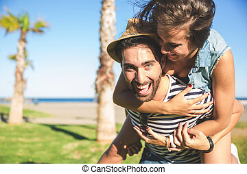 Happy man giving his girlfriend piggyback ride