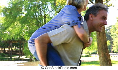Happy man giving his partner a piggy back ride