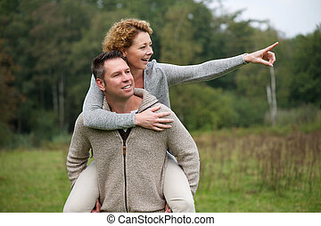 Happy man giving smiling woman piggyback ride