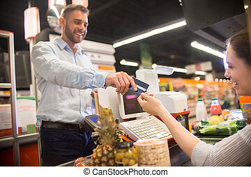 Happy Man Handing Credit Card to Cashier in Supermarket