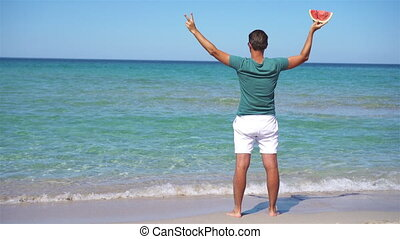 Man relaxing on the beach smiling with a slice of watermelon in hand