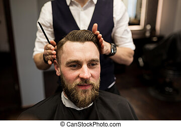 Happy man having hair cut at barber salon