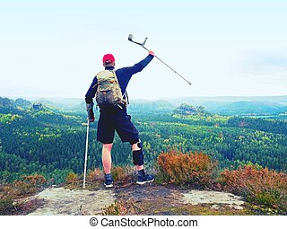 Happy man hiker holding medicine crutch above head, injured ...