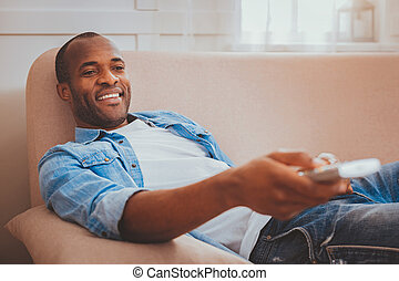 Happy man holding a remote control
