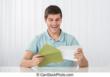 Happy Man Holding Letter On Desk