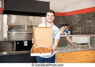 Happy man holding open pizza box