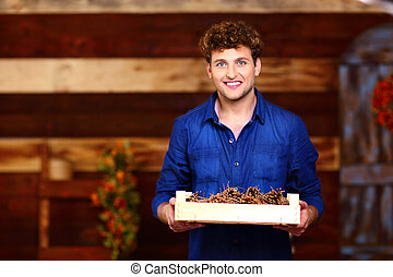Happy man holding wooden box with pine cones