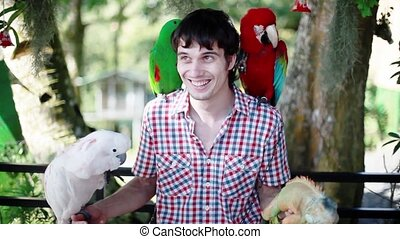 Happy man holds blue-gold Macaw parrot white parrot macaw...