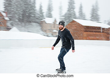 Happy man ice skating outdoors