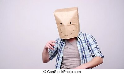 Happy man in a paper bag dancing on a gray background -...