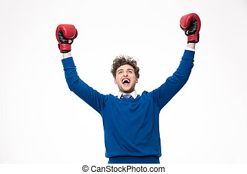 Happy man in boxing gloves celebrating a win over white background