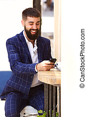 Happy man in business suit sitting with mobile phone
