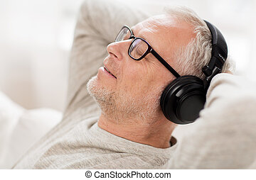 happy man in headphones listening to music at home -...