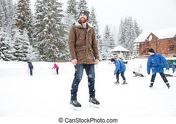 Happy man in ice skates looking away outdoors