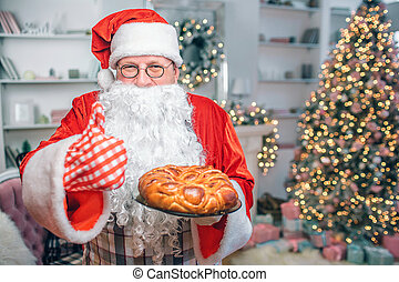 Happy man in Santa Claus clothes holds pie and shows big thumb up. Guy looks on camera. He is in festive room alone.