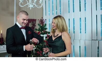 Happy Man in Suit and Woman in Evening Dress Champagne explosion in a white room with fireplace and Christmas tree