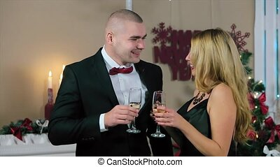 Happy Man in Suit and Woman in Evening Dress Hold glasses in a white room with fireplace and Christmas tree