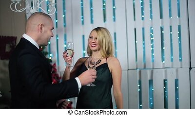 Happy Man in Suit and Woman With a Wide Smile in evening dress knocking glasses in a white room with fireplace and Christmas tree