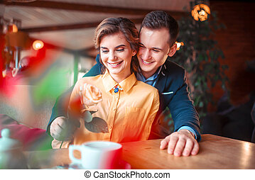 Happy man in suit gives rose to beautiful woman