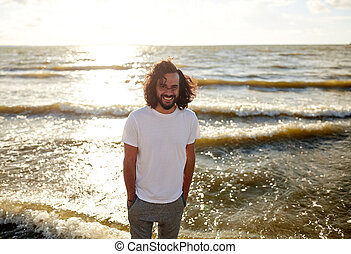 happy man in white t-shirt on beach over sea