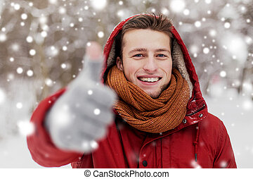 happy man in winter jacket showing thumbs up - people,...