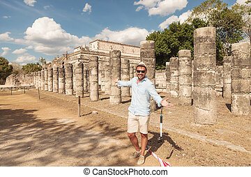 Happy man inviting you to visit the ruins