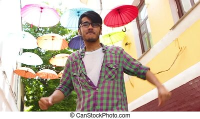 Happy man is dancing under colorful umbrellas on the street