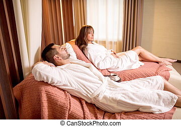 happy man is lying on the bed and sleeping while his wife sitting with pensive look