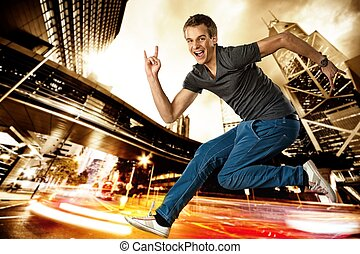 Happy man jumping against night city