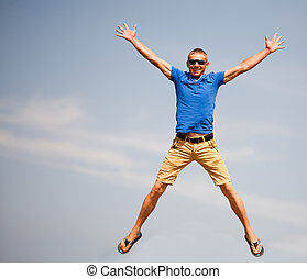Happy man jumping, blue sky on background