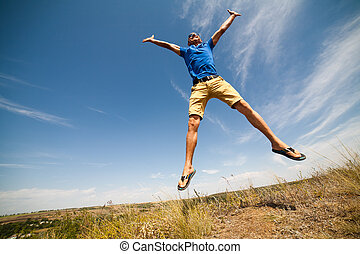 Happy man jumping, blue sky on background, wide angle