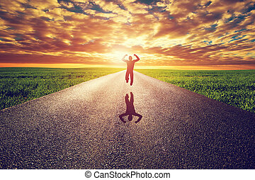 Happy man jumping on long straight road, way towards sunset sun