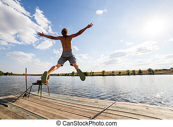 Happy man jumping on pier with lake and sky in background