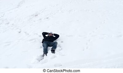 """""""Happy man lie down in snow, lying white background"""""""