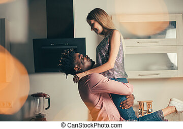 Happy man lifting his girlfriend up and smiling