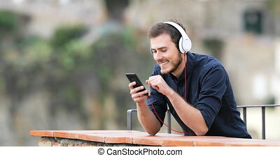 Happy man listening to music from phone in a balcony - Happy...