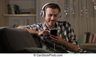 Happy man listening to music on phone in the night - Happy...