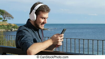 Happy man listening to music sitting on a bench