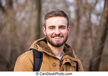 Happy man looking at camera outdoors