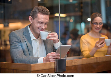Happy man looking at gadgets in cafe
