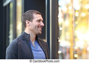 Happy man looking at storefront in the street