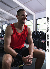 Happy man looking away while sitting in fitness center