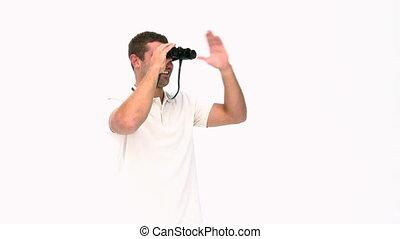 Happy man looking through binoculars against a white...