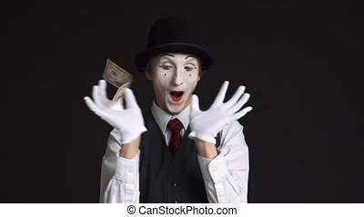 happy man mime holding a 50 dollar bill on black background