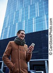 Happy man noting in phone