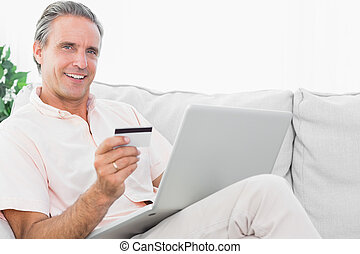 Happy man on his couch using laptop for shopping online