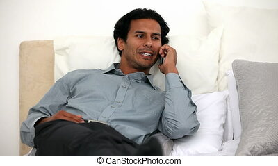 Happy man on the phone on his bed