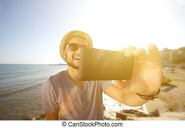 Happy man on vacation taking a selfie at the beach