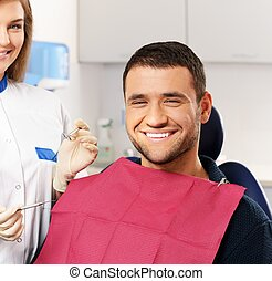 Happy man patient and smiling woman dentist at dental surgery